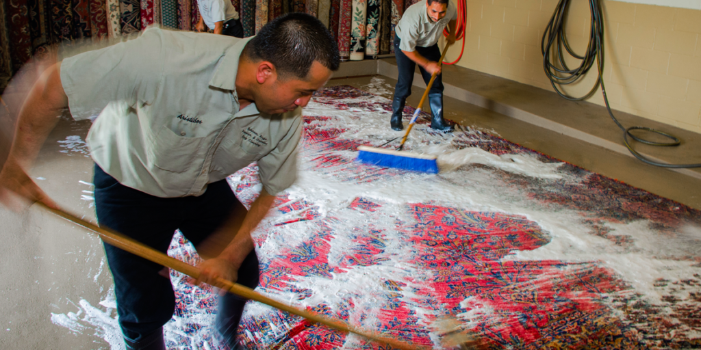 Persian rug cleaners cleaning a rug using traditional handwashing methods.